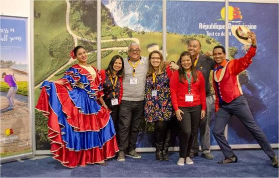 Cosette Garcia, en avant, directrice du Bureau de la Promotion du tourisme de la République dominicaine ainsi que ses assistants : Luiz Mustafa, Elsa Montalvo, Paola Gomez et Roberto Mejia, entourés des danseurs dans leur costume traditionnel.