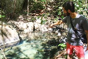 Gabriel Saragovia, responsable des marchés du Rio Perdido, nous montre les sources thermales qui émergent sous les rochers et réchauffent les bassins de la rivière.
