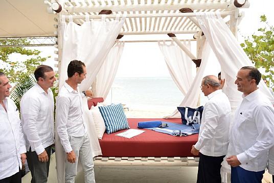 Xavier Mufraggi (à gauche), Président Directeur Général Club Med Amérique du Nord et H. E. Danilo Medina Sánchez (à droite), Président de la République dominicaine, ouvrant officiellement les rideaux sur le premier élément iconique de Club Med Michès – la première palapa – durant l'évènement de première pelletée officielle'